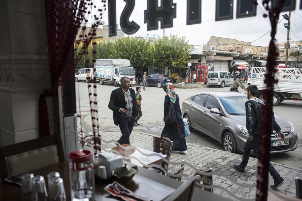 In downtown Midyat, a city with a mixed population of Turks, Syriac's and, Armenians. Through the window of a restaurant a woman walks down the main street on October 31st, 2014.