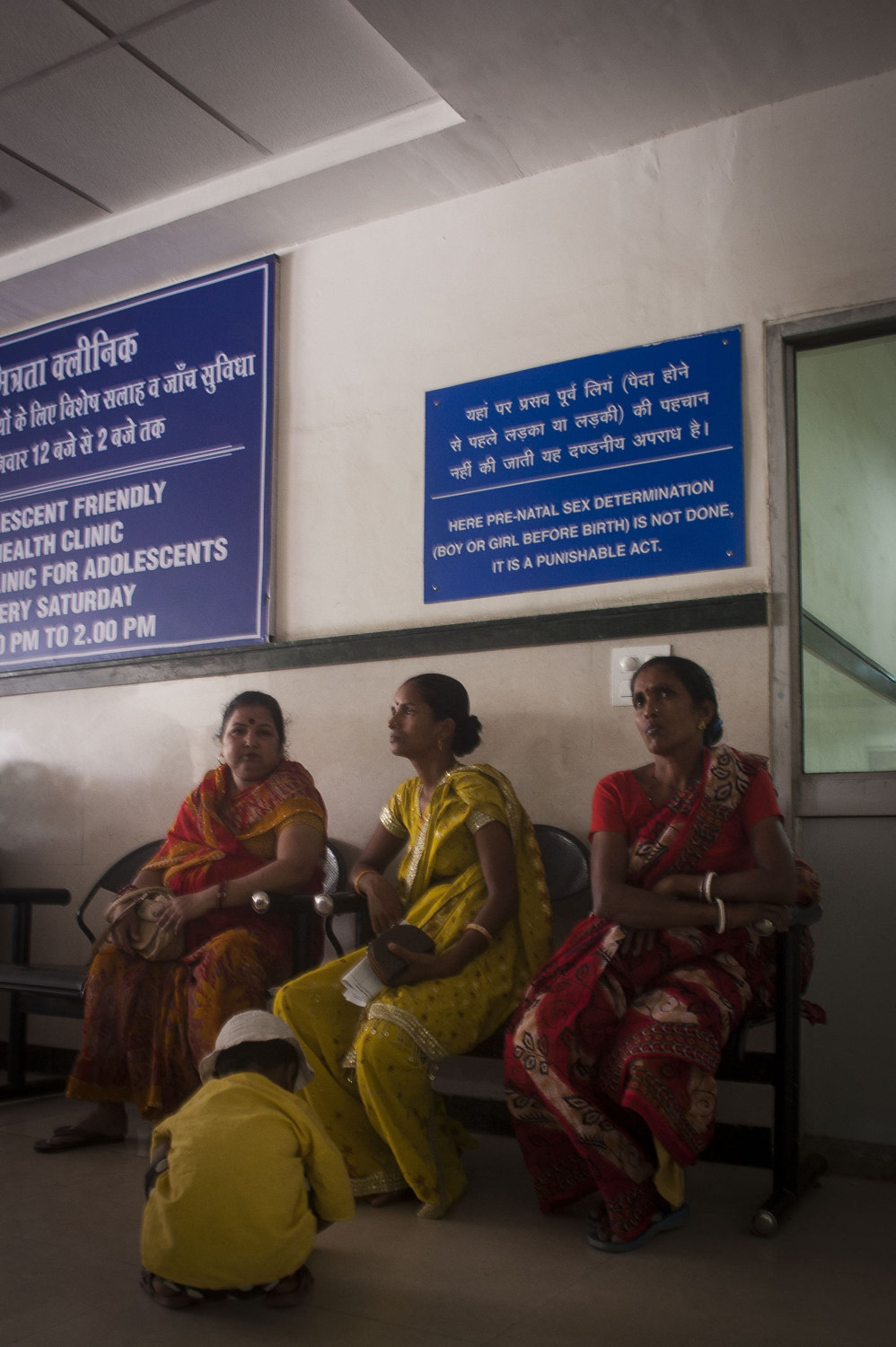 Woman in front of a sign declaring that ultrasounds to determine sex are illegal at the Gurgaon Hospital outside of New Delhi, India.
