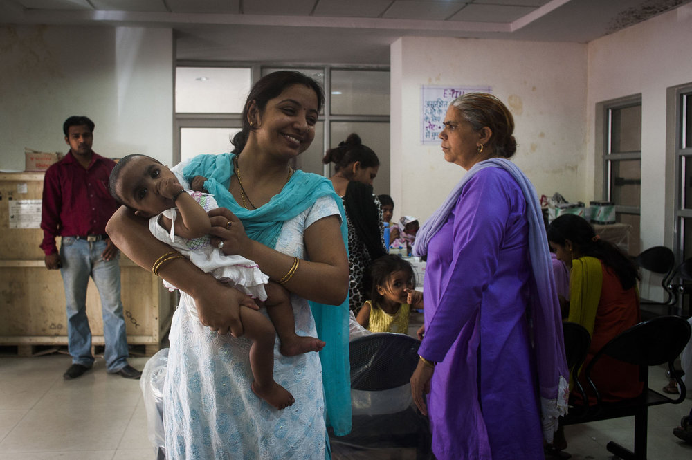 A young mother and her daughter, visit the Gurgaon hospital so the baby can receive typical vaccinations. In India the emphasis on two children per household has caused riffs in many families that already have one girl.