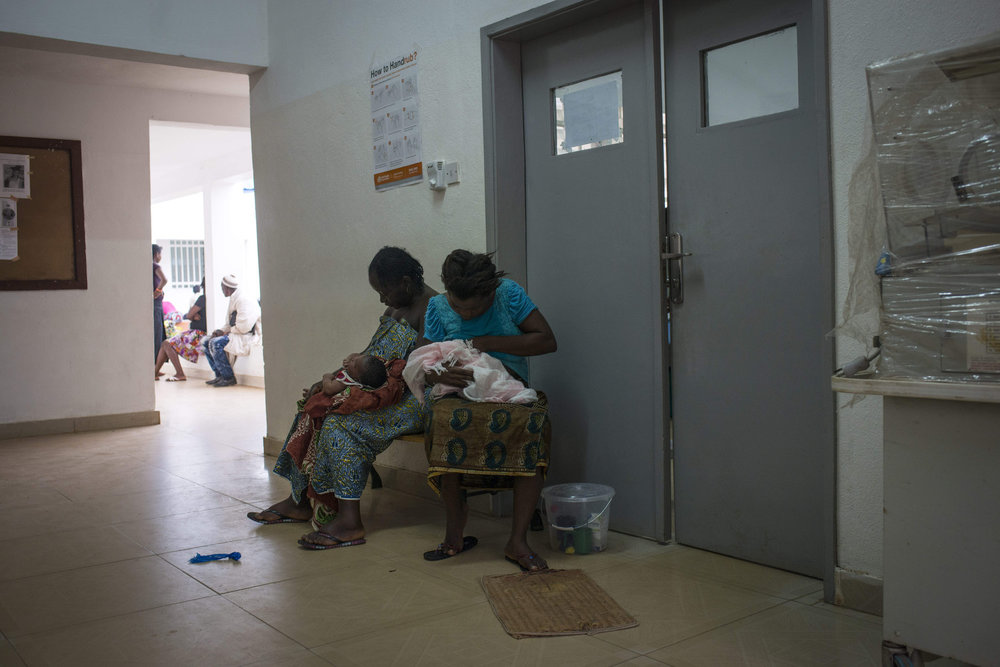 Nurses preform post- natal checkups on babies brought to the NICU ward. There they check the temperature and give injections. At Kenema Government Hospital in Kenema, Sierra Leone on November 10th, 2015.
