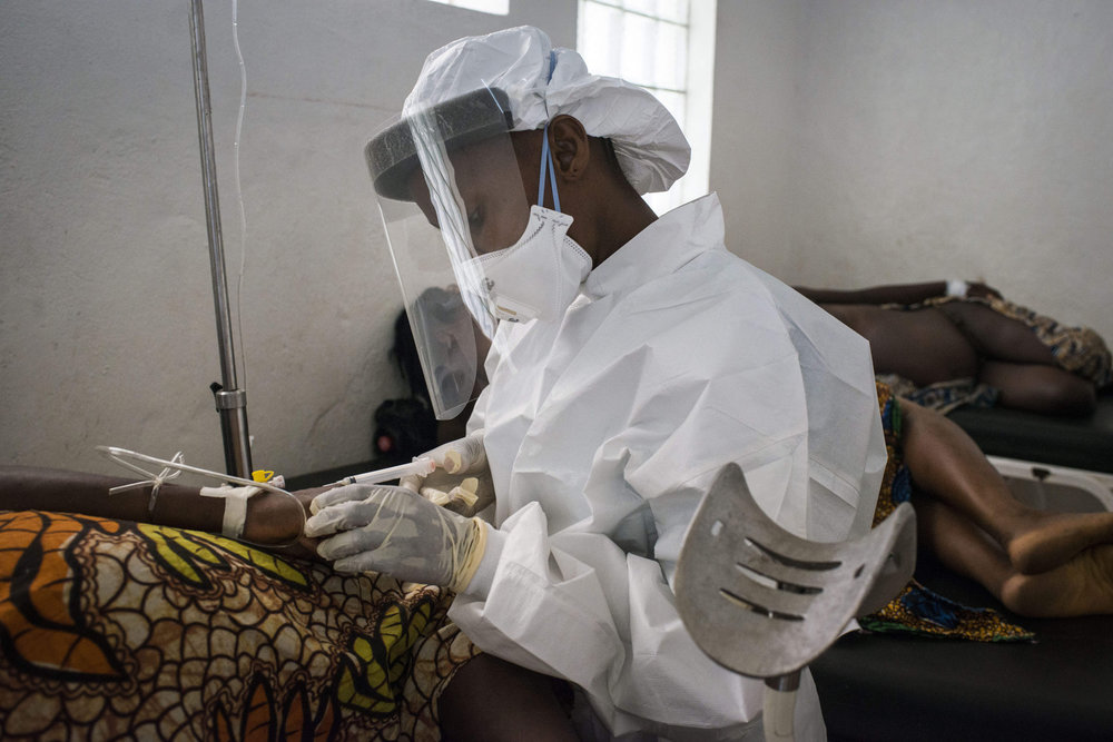 A nurse takes blood from Kema James after she delivers. Full body protection is used to collect blood samples as Ebola is still a precaution in Sierra Leone.