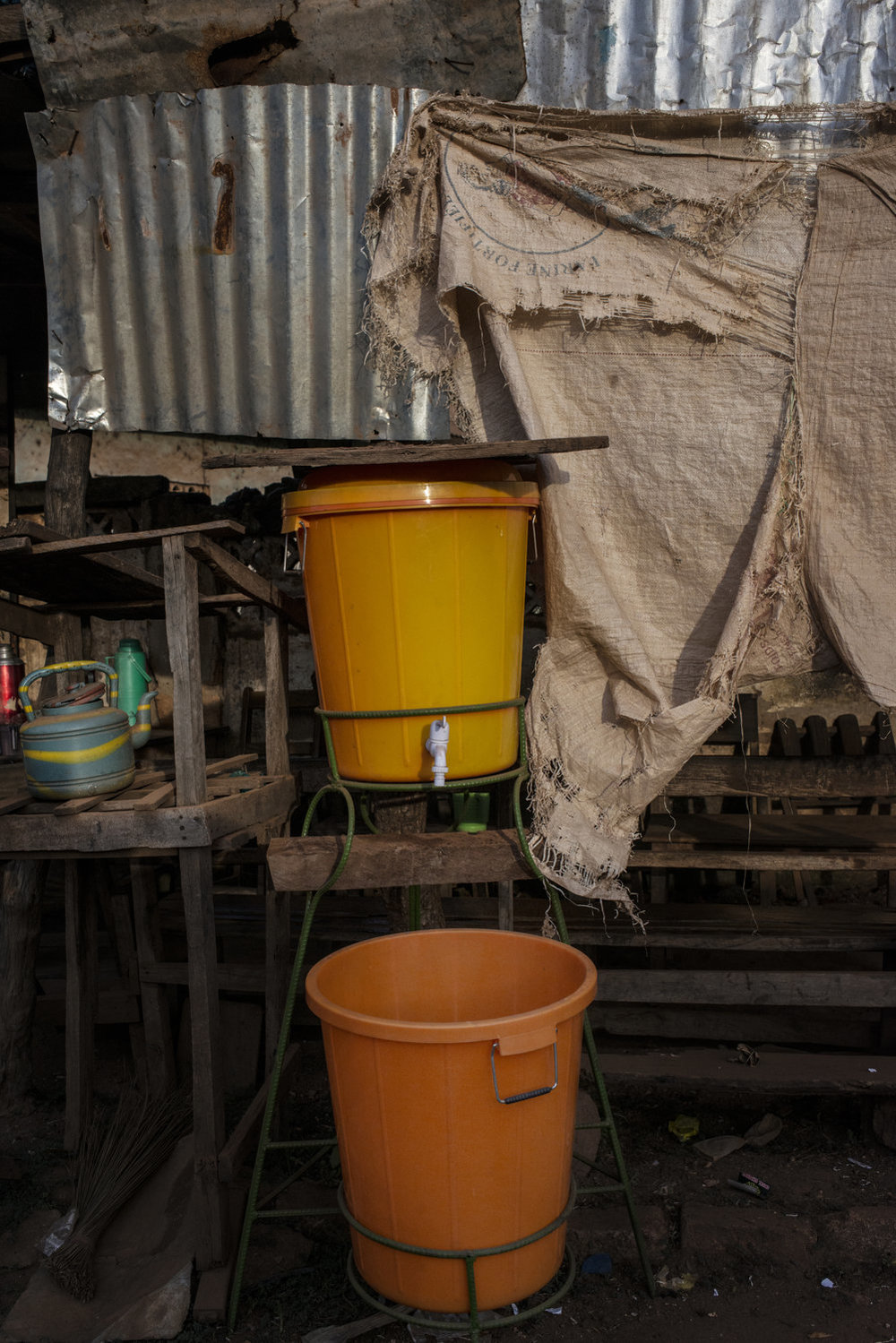 A hand washing stand near the market in Faranah, Guinea. The stands contain a mixture of bleach and water which kills germs including ebola. These colorful basins can be found throughout the country.