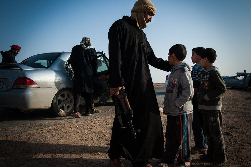 A man and his sons watch as fighters load into a car and head south to the battle.