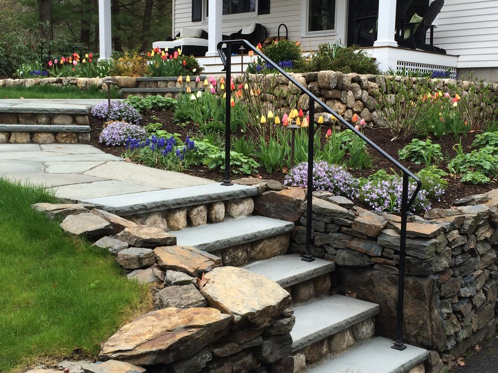 Redesigned granite topped fieldstone steps lead from the driveway up to the front door and deck. The low granite wall solves the grading issues and provide a structure for the planting beds.