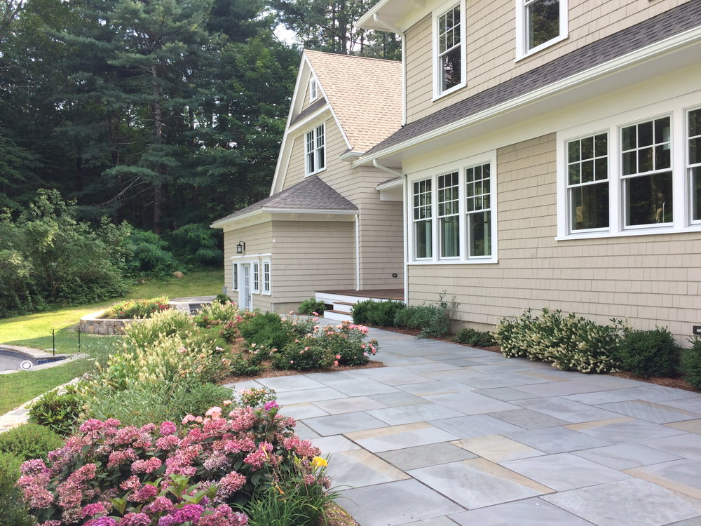 A large bluestone patio allows lots of space for outdoor furniture. It is softened by plantings of low maintenance small shrubs which add summer color and highlight views from the patio.
