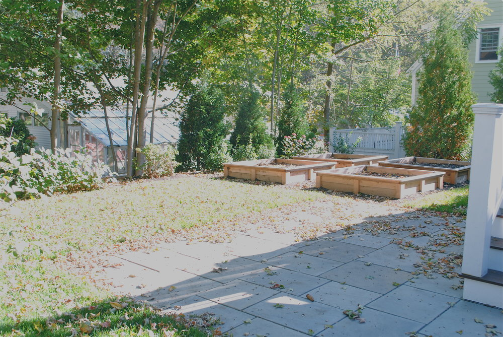 Regrading maximizes the space in this back yard and allows for a stone patio at the base of the stairs and for four raised vegetable beds.
