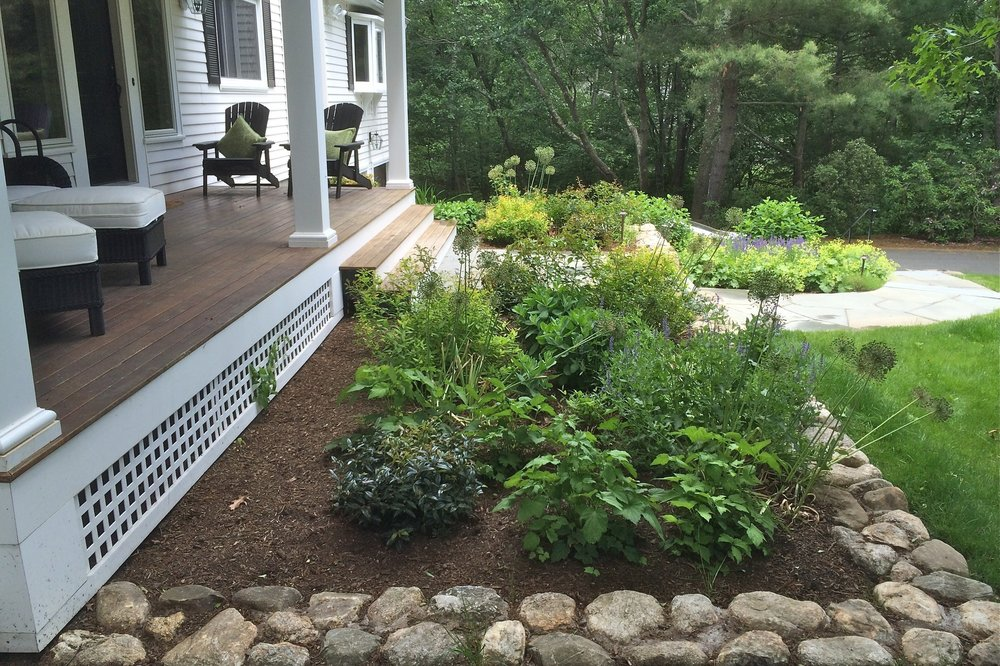 A view of small shrubs and flowers enclosed by a stone wall makes this deck a great place to sit.