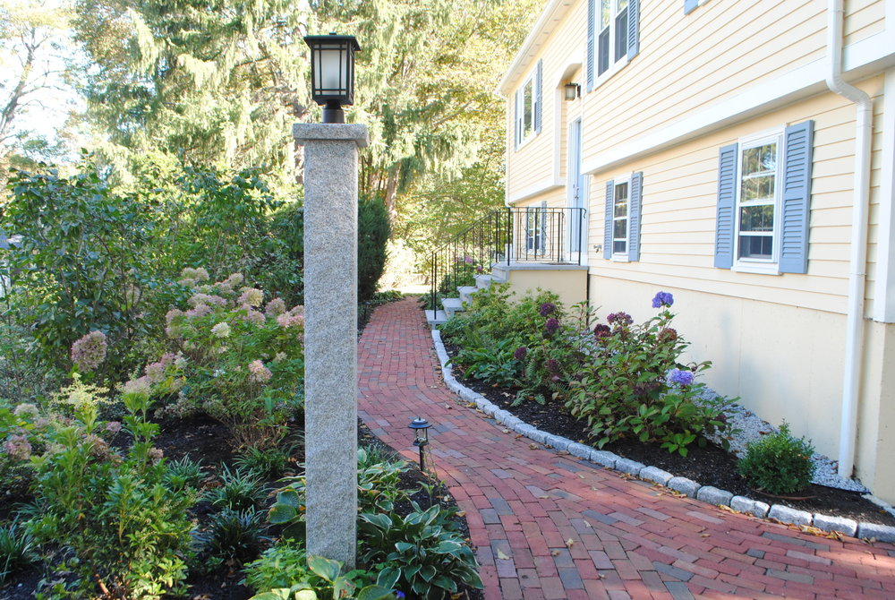 "A brick path is restored and splays out to meet the driveway. Borders of shade tolerant shrubs line the foundation and a lamppost ""announces"" the side entrance to the house."