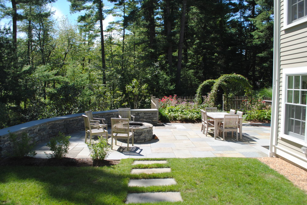 An enclosed patio with a fire pit and sitting walls connects to a small formal garden with arches for roses and flowering vines, and flowers.