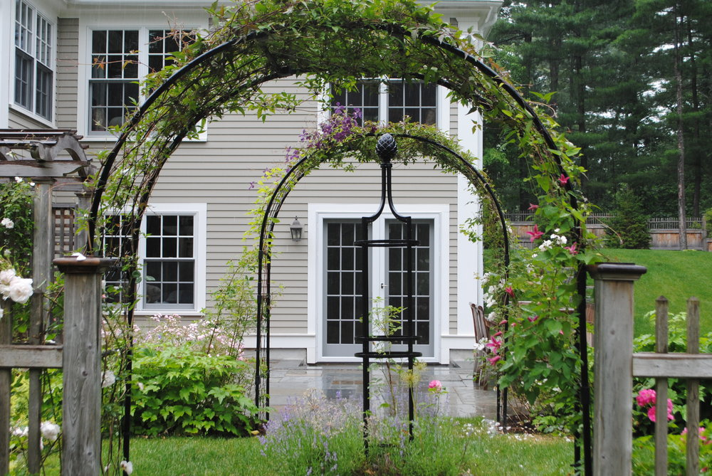 Small rose garden with Monet arches leads off from the patio creating another outdoor room.