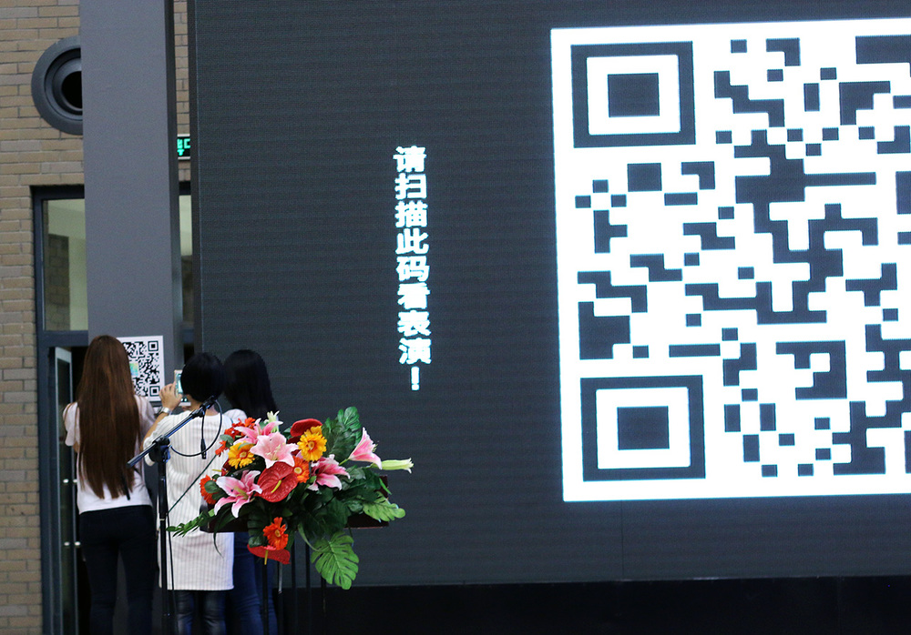 "The audience are scanning the     QR code to join the ""group chatting"""