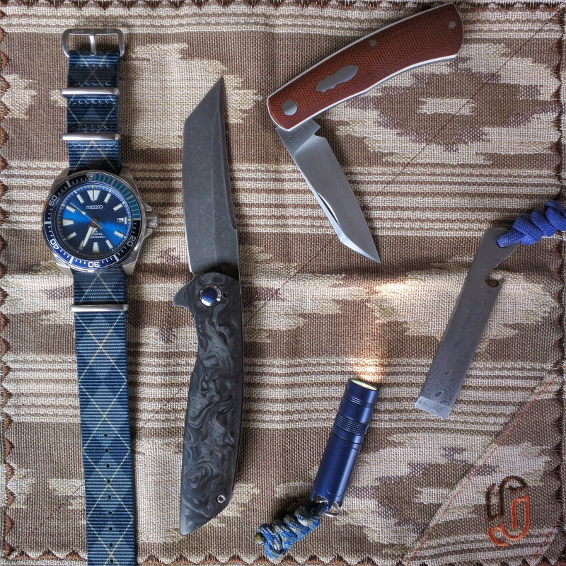 Pictured: FoxHanx Handkerchief, Seiko Samurai Blue Lagoon LE, Snyder Knives Delta One, Muyshondt Maus, Sharpwerks Pocket Tool, Jared Oeser Native