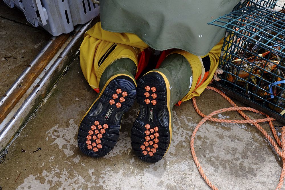 The shoes of a lobsterman are designed to grab onto a wet boat.  They wear a lot of heavy clothing.  I wonder how they manage being in it all day.