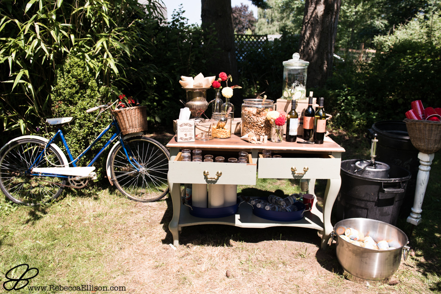 snacks table at wedding ceremony using vintage furniture, styled with old bicycle