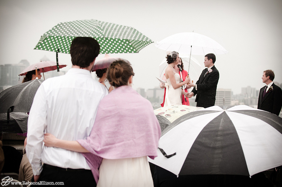 guests watch Gasworks park wedding ceremony under an umbrella