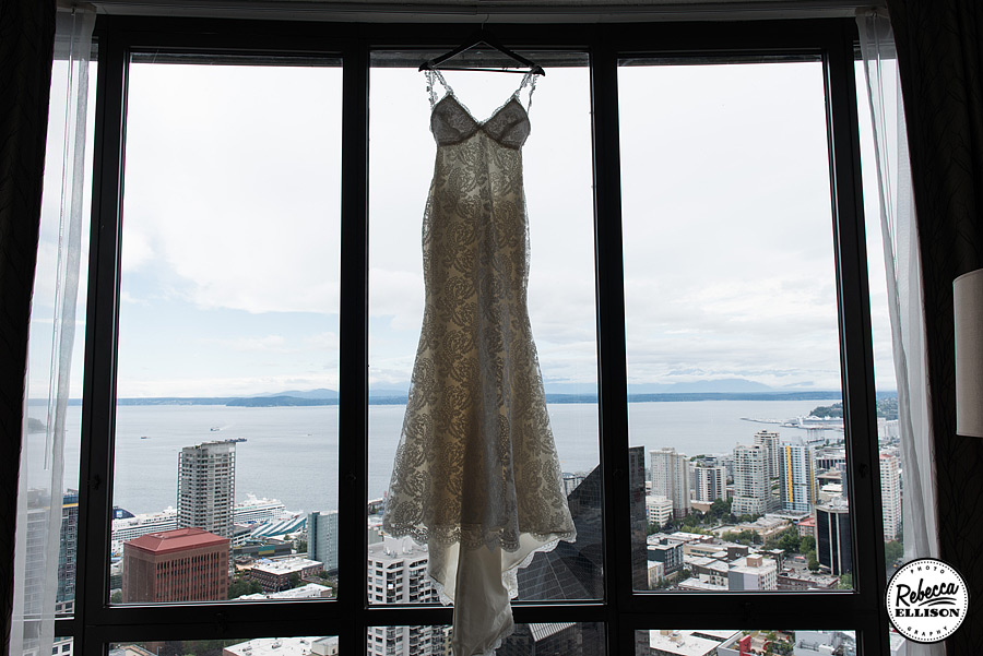 Katie May Lace wedding gown hangs in a window overlooking downtown Seattle photographed by Seattle wedding photographer Rebecca Ellison