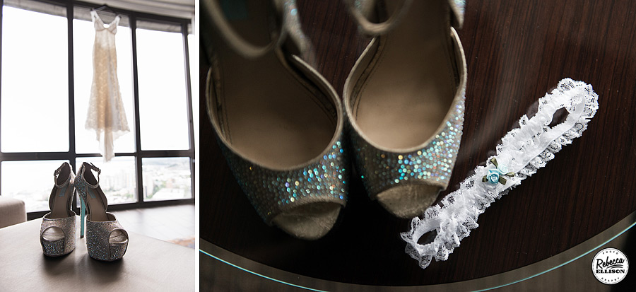 Bridal details include white sparkly Betsey Johnson peep toe heels and a white lace garter with a blue rose while the Katie May wedding dress hangs in the background photographed by Seattle wedding photographer Rebecca Ellison