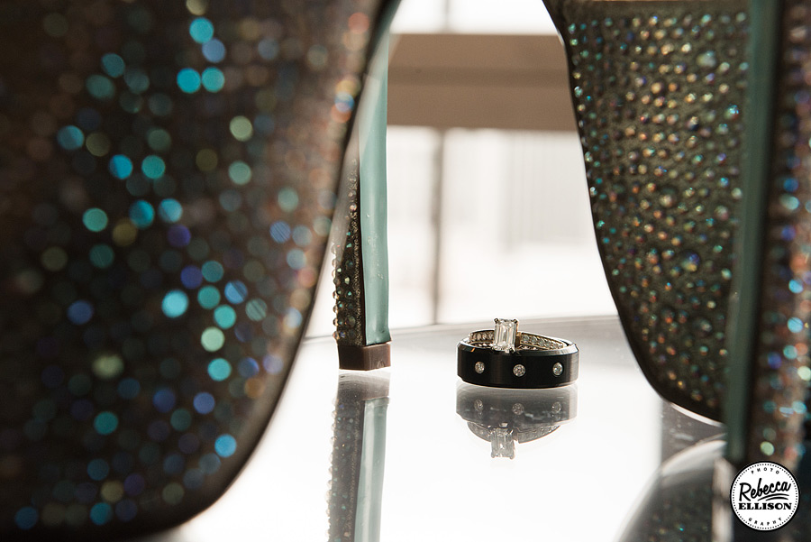 Wedding ring sits in between the heels of sparkly white wedding shoes photography by Rebecca Ellison