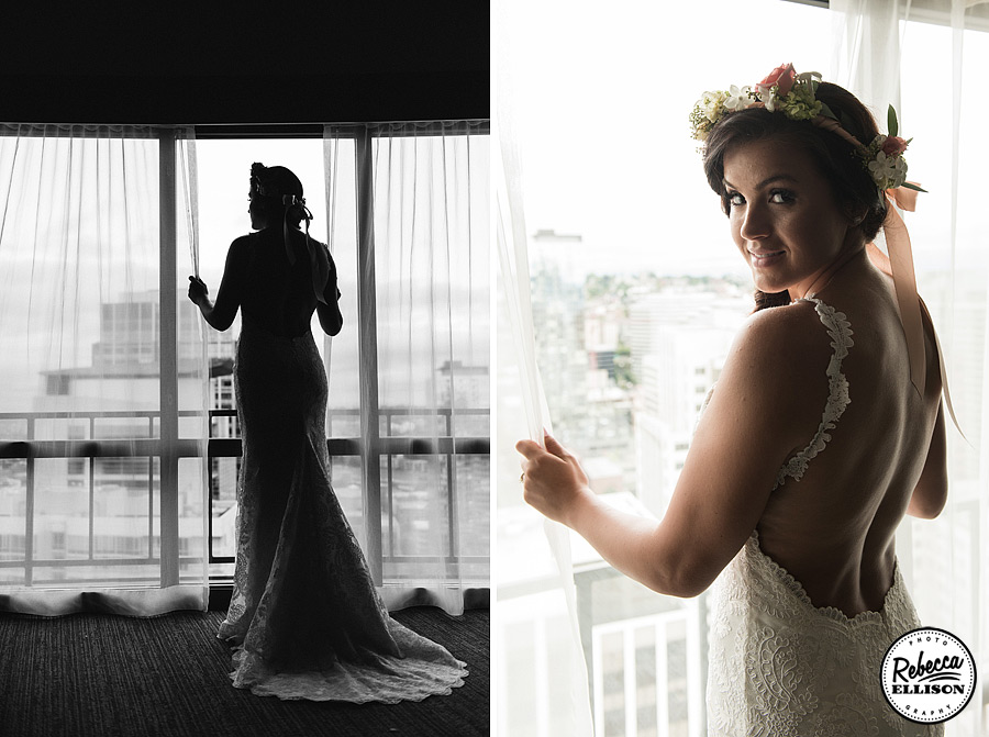 Bride stands in a window overlooking downtown Seattle in a white lace backless wedding gown and a crown of flowers photographed by Seattle wedding photographer Rebecca Ellison
