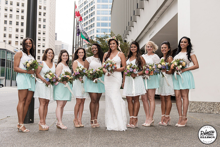 Bridal party portraits in Downtown Seattle featuring light blue and white bridesmaids dresses and spring colored flowers photographed by Rebecca Ellison Photography