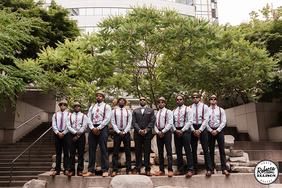 Groomsmen in Slacks, brown shoes, suspenders and red and grey ties stand on a fountain in downtown Seattle photographed by Seattle wedding photographer Rebecca Ellison