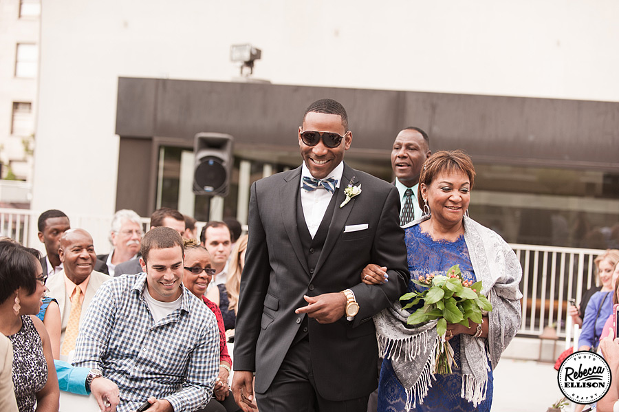 Groom escorts his mother down the aisle at a Rainier Rooftop Park wedding photographed by Seattle wedding photographer Rebecca Ellison