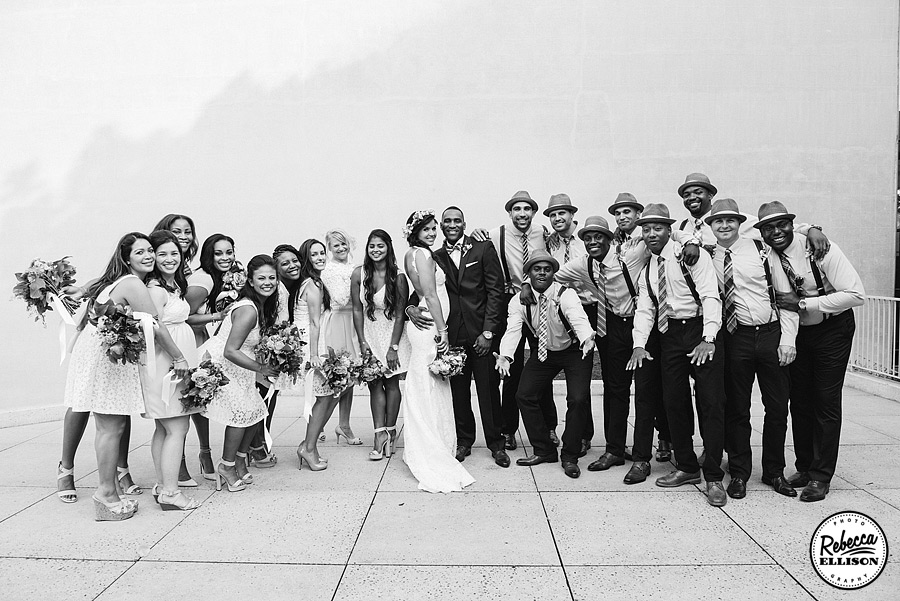 Black and white wedding party portrait featuring fedoras and a backless Katie May wedding dress photographed by Rebecca Ellison Photography