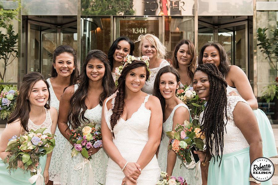 Outdoor bridal party portraits in Downtown seattle featuring white and blue bridesmaids dresses and spring colored flowers photographed by Rebecca Ellison Photography