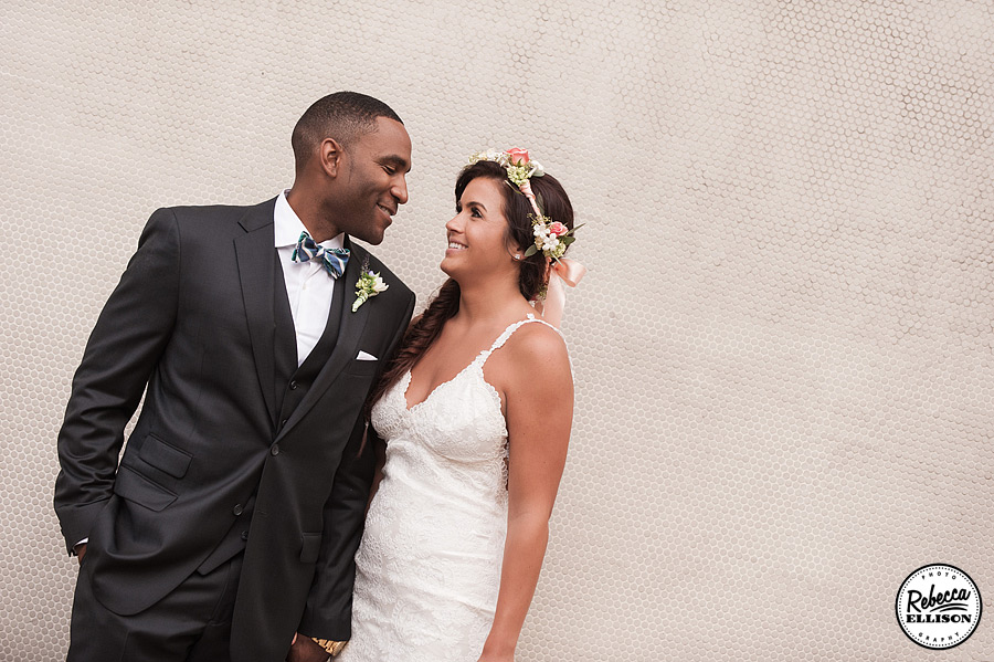 Bride and groom during outdoor wedding portraits in Downtown Seattle featuring a bowtie, white lace Katie May wedding dress and a crown of flowers photographed by Rebecca Ellison Photography