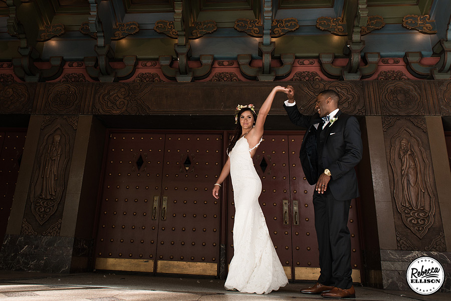 Bride and groom dance in front of ornate doors during downtown Seattle wedding portraits by Seattle wedding photographer Rebecca Ellison