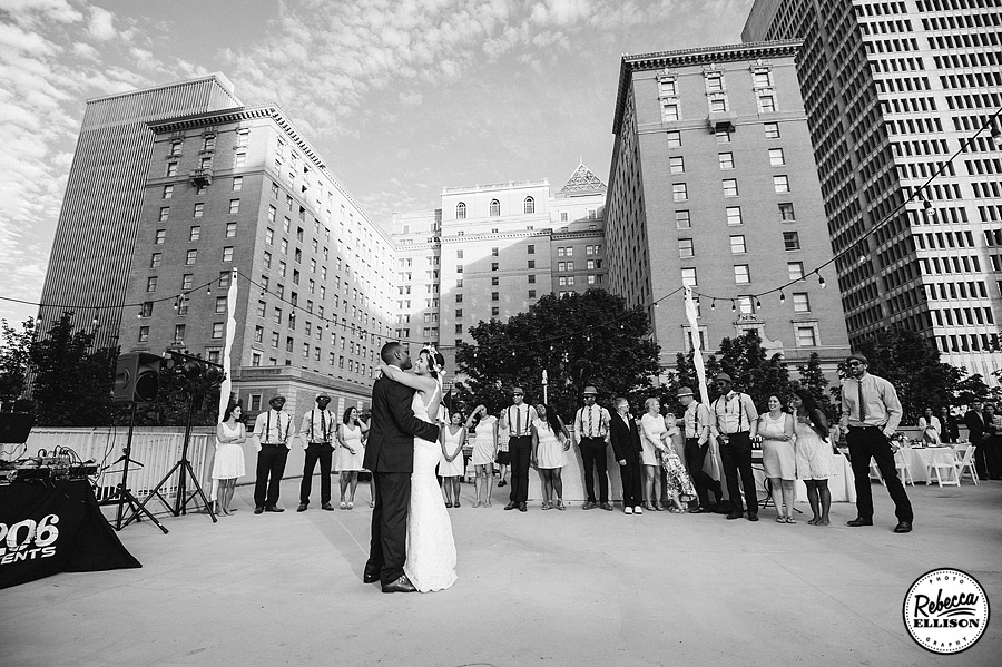 Bride and groom dance against the Seattle Skyline at their Rainier Rooftop park wedding reception photography by Rebecca Ellison