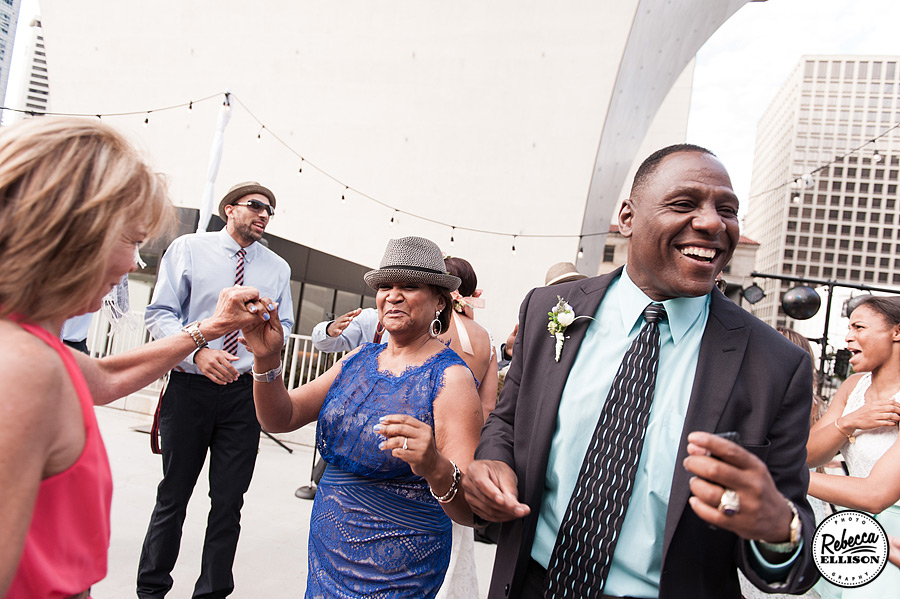 Wedding guests dance at an outdoor wedding reception at Rainier Rooftop park in Seattle photography by Rebecca Ellison