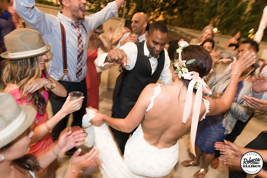 Bride and groom dance at their wedding reception featuring a white backless wedding dress and a crown of flowers photographed by Rebecca Ellison Photography