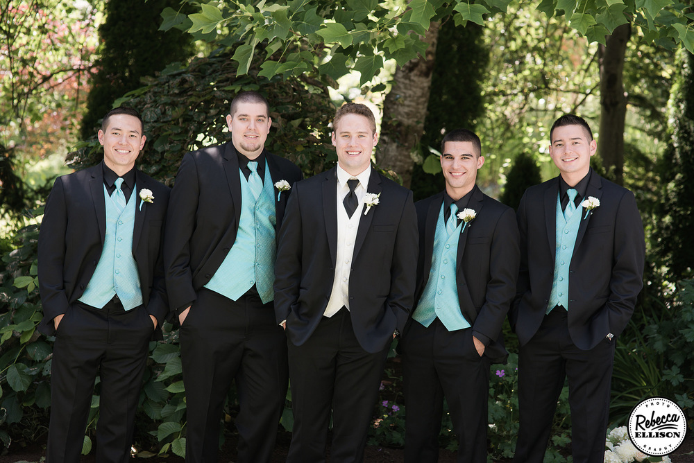 Groomsmen stand in front of a group of trees during outdoor wedding portraits featuring black suits with blue vests and ties photographed by Seattle wedding photographer Rebecca Ellison