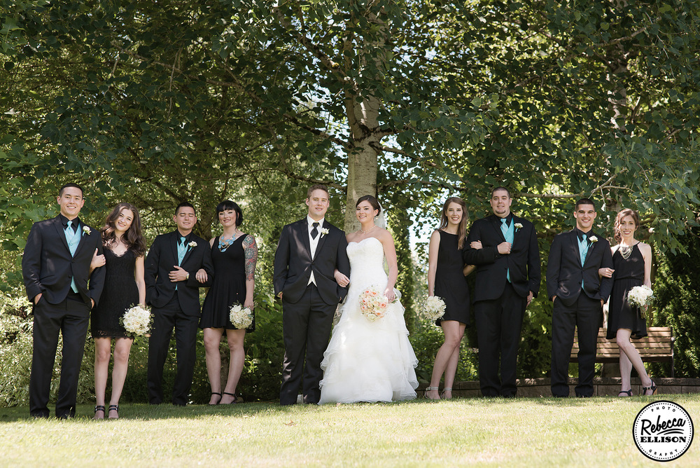 Wedding party stands under a huge oak tree featuring black bridesmaids dresses, black suits with blue vests and ties photographed by Rebecca Ellison Photography