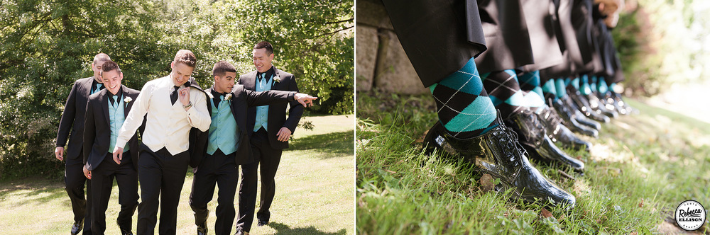 Groomsmen during outdoor wedding portraits walk through a garden wearing black suits with blue vests and ties and black and blue argyle socks