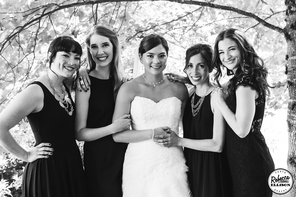 Black and white bridal party portrait during outdoor wedding photos featuring black bridesmaids dresses and white strapless wedding dress photographed by Seattle wedding photographer Rebecca Ellison