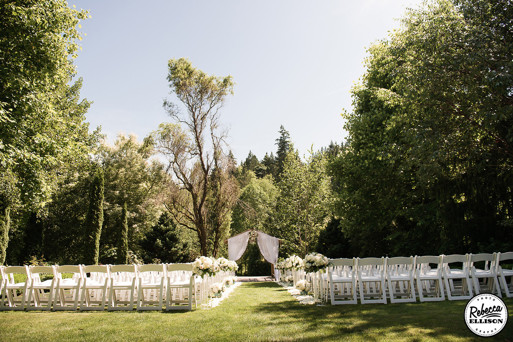 Wedding ceremony at an outdoor garden wedding surrounded by trees on a sunny day photographed by Seattle wedding photographer Rebecca Ellison