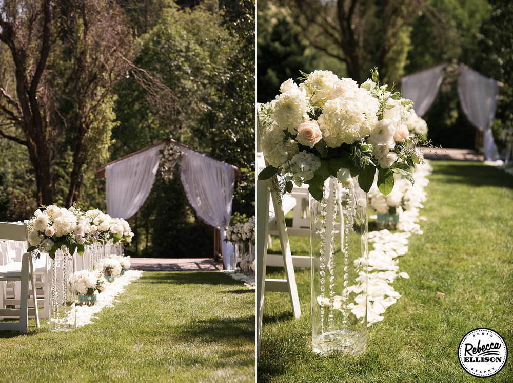 Wedding ceremony details at an outdoor garden wedding featuring a wooden arbor with billowing white curtains and clear vases lined with crystals and filled with white flowers line the aisle photographed by Seattle wedding photographer Rebecca Ellison