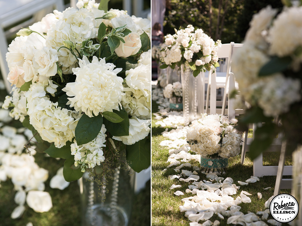 Wedding aisle lined with vases of varying height filled with white flowers and crystals photographed by Seattle wedding photographer Rebecca Ellison