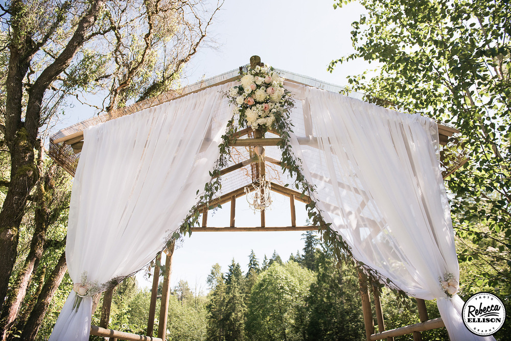 Wooden wedding arbor decorated with billowing white curtains, flowers, leaves and a crystal chandelier at an outdoor garden wedding photographed by Rebecca Ellison Photography