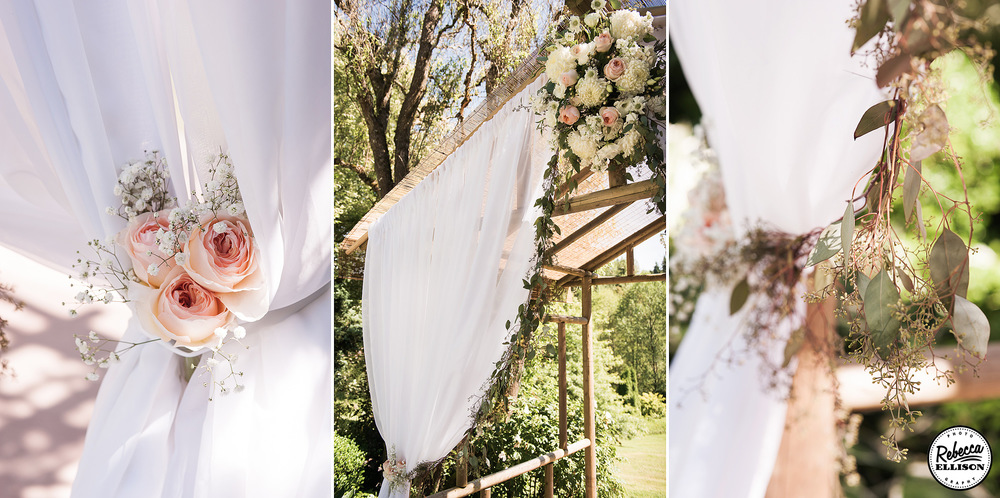 White curtains, peach roses, white flowers and leaves decorate a wooden wedding arbor at an outdoor garden wedding photographed by Seattle wedding photographer Rebecca Ellison