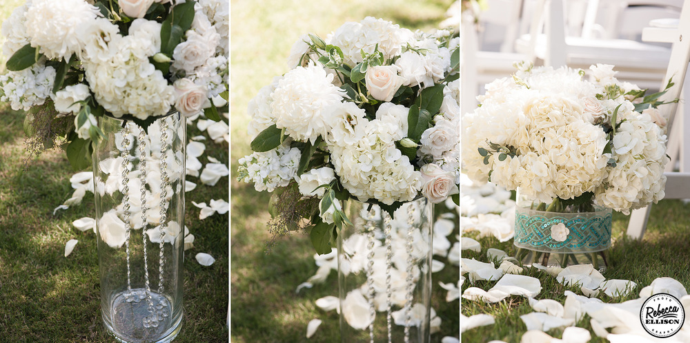 vases filled with crytals and white flowers line the wedding aisle at an outdoor garden wedding photography by Rebecca Ellison