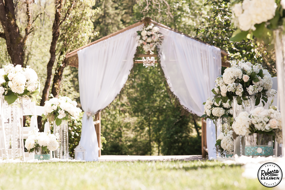 Wedding details at an outdoor garden wedding featuring a wooden arbor, white curtains and a flower lined wedding aisle photographed by Rebecca Ellison Photography