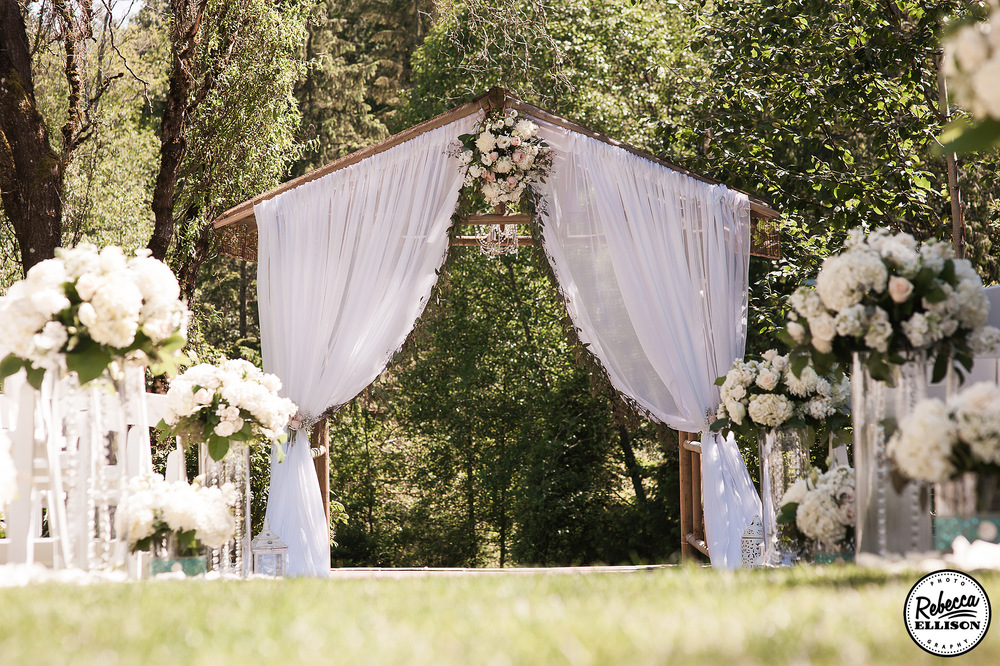 Outdoor garden wedding featuring a flower lined aisle and a wooden arbor decorated with flowers and white curtains photographed by Rebecca Ellison Photography