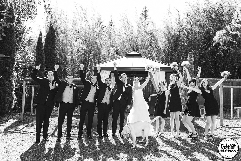 Wedding party celebrates after the ceremony in a black and white outdoor wedding portrait photography by Rebecca Ellison