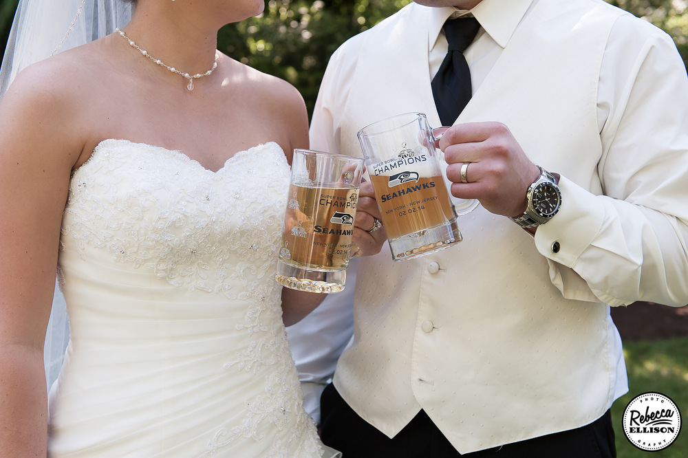 Bride and groom drink beer out of Seattle Seahawks beer steins at their outdoor garden wedding photographed by Seattle wedding photographer Rebecca Ellison