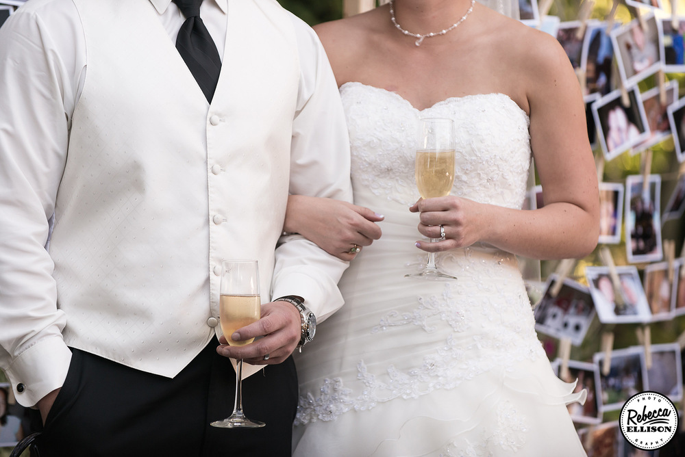 Bride and groom hold their champagne flutes for toasts in front of a photo display photographed by Rebecca Ellison Photography