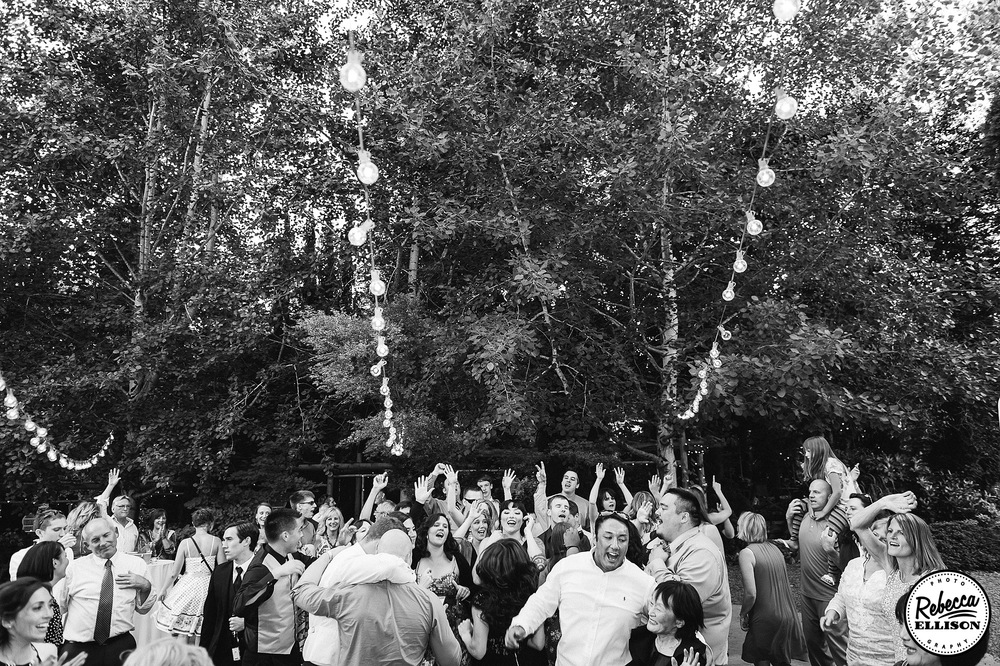 Wedding guests dance at an outdoor wedding reception featuring a forest of trees and lightbulb strings photographed by Rebecca Ellison Photography