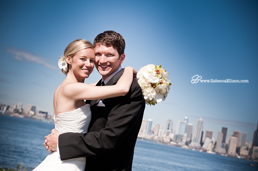 a bride and groom hug on Alki beach with seattle skyline in the background